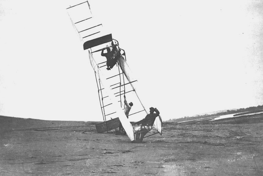 Machine_turning_over_with_Orville_Wright_aboard_Kitty_Hawk_NC_1911.10470_A.S.